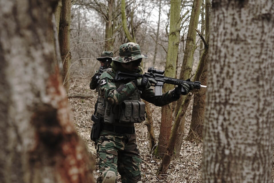 Two people in military clothing playing airsoft in a forest